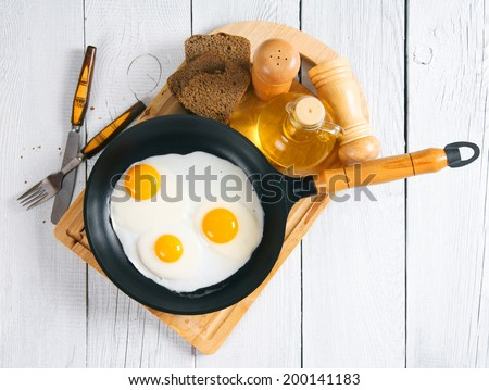Fried eggs in a frying pan, an olive oil, rye bread, a saltcellar and tablewares on a chopping board. On a wooden background. - stock photo