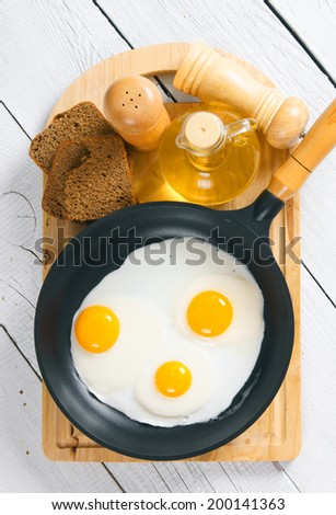 Fried eggs in a frying pan, an olive oil, rye bread, a saltcellar on a chopping board. On a wooden background. - stock photo
