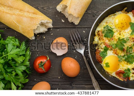 Fried eggs in a frying pan, fork, spoon, towel, herbs, eggs - stock photo
