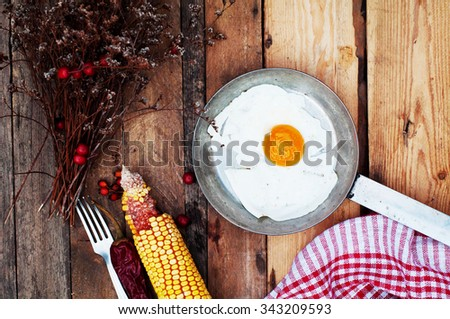 Fried eggs in a frying pan on wooden background. Breakfast. Healthy food. Fried eggs. Fried egg on a pan . Rustic food style. Ripe corn. Food and drink. - stock photo