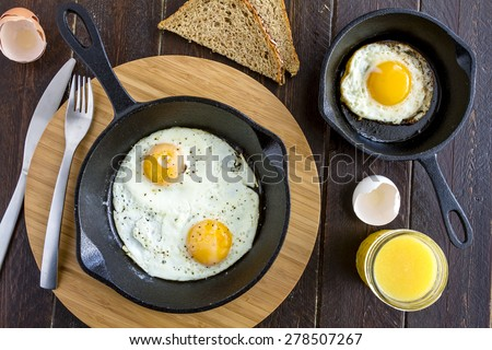 Fried eggs in cast iron skillet sitting on kitchen table with whole wheat toast and orange juice - stock photo