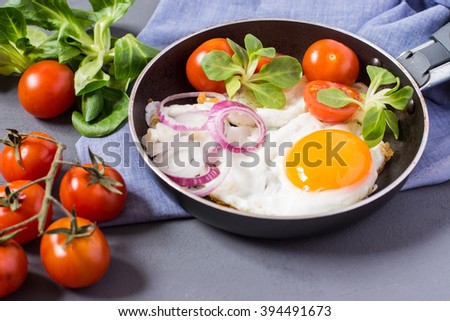 Fried eggs in frying pan with tomatoes, onion, spinach for breakfast or lunch - stock photo