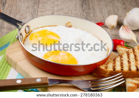 Fried eggs in frying pan with vegetables aside - stock photo
