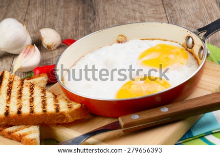 Fried eggs in frying pan with vegetables aside rustic style - stock photo