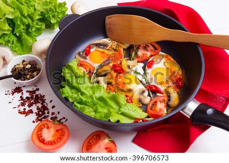 Fried eggs in pan with ingredients on wooden background - stock photo
