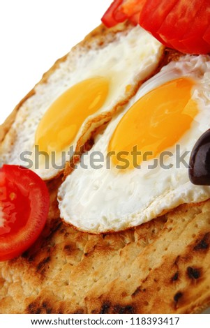 fried eggs on pancake with tomato and olives - stock photo