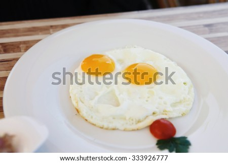 fried eggs on white plate - stock photo