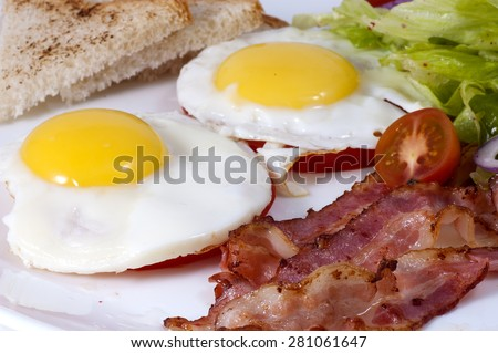 fried eggs with bacon and lettuce closeup on a white plate. - stock photo