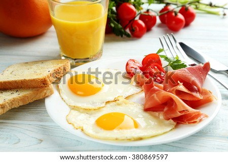 Fried eggs with bacon and toasts on plate on blue wooden table - stock photo