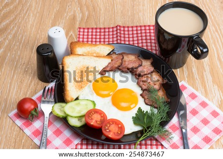 fried eggs with bacon, bread, coffee and vegetables on black dish - stock photo