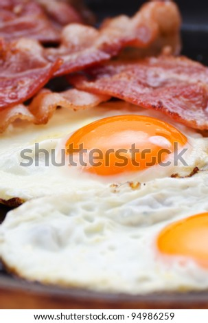 Fried eggs with bacon in a pan - stock photo
