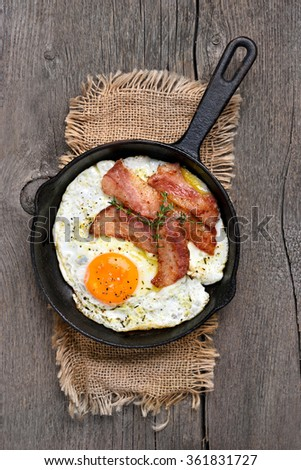 Fried eggs with bacon in frying pan, top view - stock photo