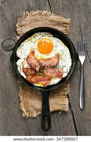 Fried eggs with bacon on wooden background, top view - stock photo