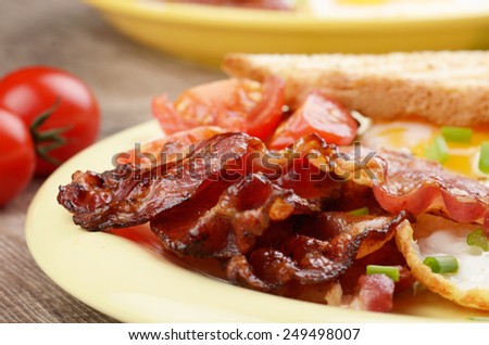 Fried eggs with bacon sausages and greens - stock photo