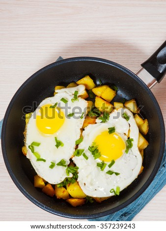 fried eggs with potato on pan - stock photo
