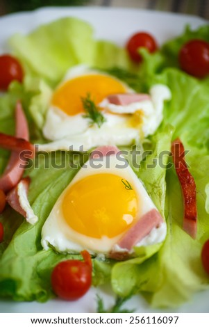 fried eggs with sausage and tomato on a plate - stock photo