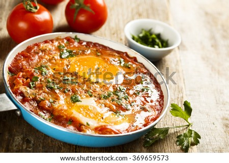 Fried eggs with tomatoes, spices and herbs - stock photo