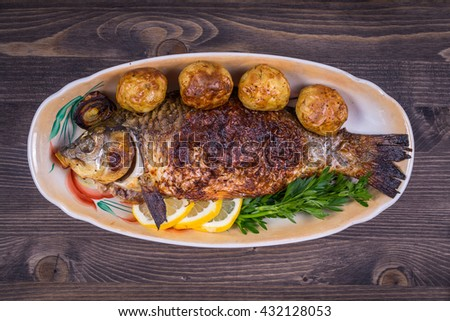 Fried fish carp on the plate, close up - stock photo