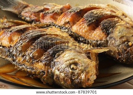 Fried fish crucian in plate - stock photo