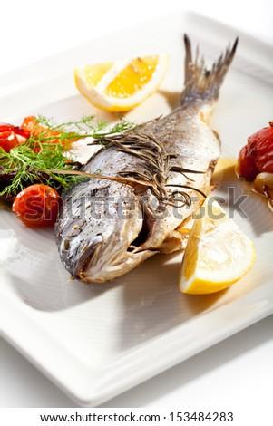 Fried Fish (Dorado). Garnished with Lemon and Vegetables - stock photo