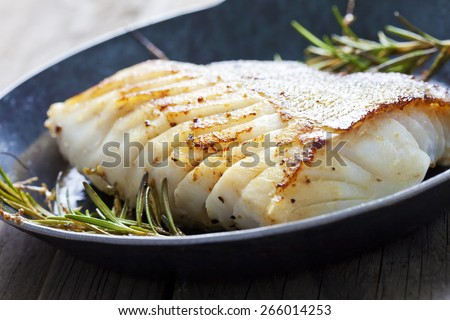 Fried fish fillet, Atlantic cod with rosemary in pan - stock photo