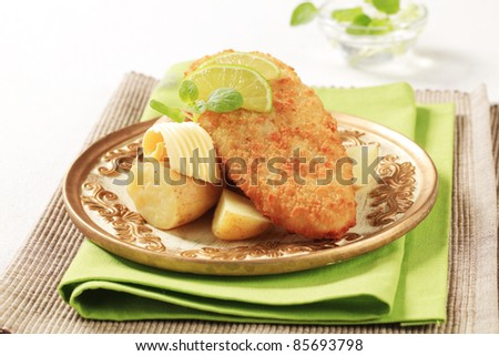 Fried fish fillet served with new potatoes - stock photo