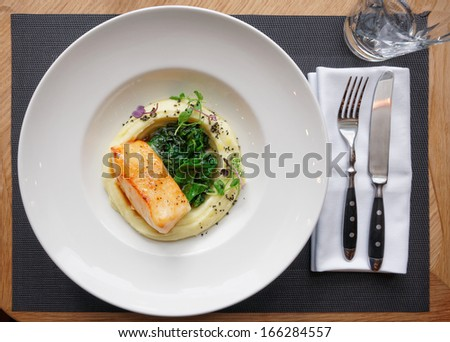 Fried fish fillet with potato mash on restaurant table - stock photo