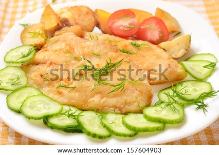 Fried fish fillet with vegetables on white plate - stock photo
