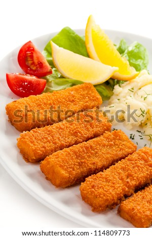 Fried fish fingers, mashed potatoes and vegetables - stock photo