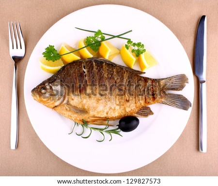 Fried fish on white plate with fork and knife, closeup - stock photo