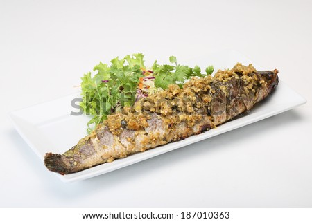 Fried fish topped with garlic served on white dish - stock photo