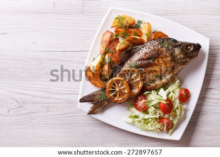 fried fish with fries and salad on a plate. horizontal view from above  - stock photo