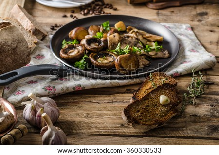 Fried fresh mushrooms with herbs, garlic toast, homemade bread - stock photo