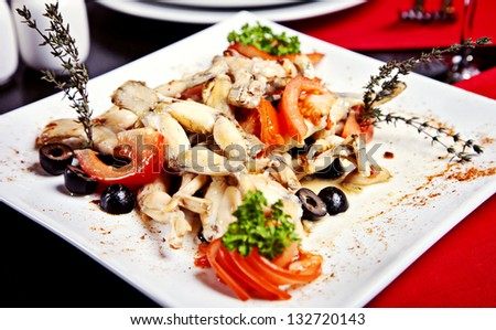 Fried frogs legs on the plate in restaurant - stock photo