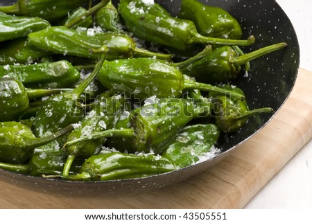 Fried green peppers Galician style in salt. Spanish cuisine. Selective focus. Pimientos de Padron. - stock photo