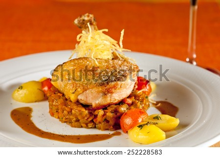 Fried guinea fowl on red lentils with red and yellow cherry tomatoes and potatoes, decorated with thyme and crispy potato straw. - stock photo