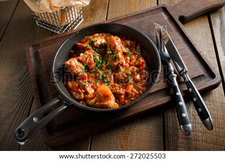 Fried meat in a frying pan in a tomato sauce with herbs, served on a wooden board with slices of toasted bread in a metal basket, lie next to a knife and fork. top view - stock photo