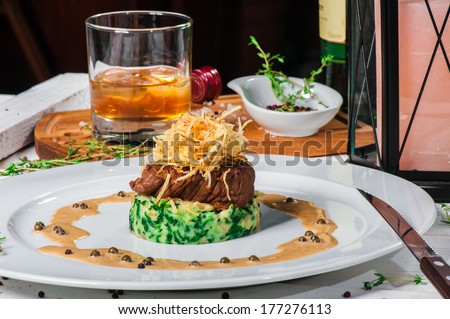 Fried meat with whiskey sauce and potato puree with spinach - stock photo