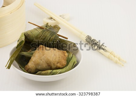 Fried minced meat mix with fish paste wrap with pandan leaf. A dim sum style Chinese cuisine prepared as small bite-size portion of food traditionally served in small steamer basket or on small plate. - stock photo