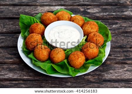 Fried mozzarella cheese stick balls with white sauce - stock photo