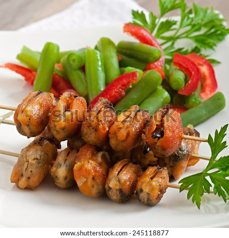 Fried mussels with onions on skewers c garnish of green beans and paprika - stock photo