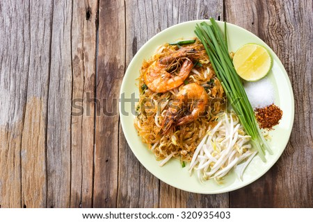 Fried noodle Thai style with prawns. On wood table. Top view. - stock photo