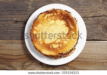 Fried pancakes in plate on rustic wooden table, top view - stock photo