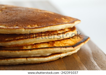 Fried pancakes on a wooden surface. - stock photo