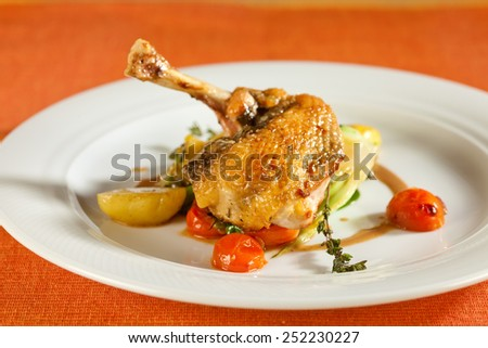 Fried pearl chicken, guinea fowl, on red lentils with vegetables and port wine sauce, decorated with very thin grilled crispy potato stripes.  - stock photo