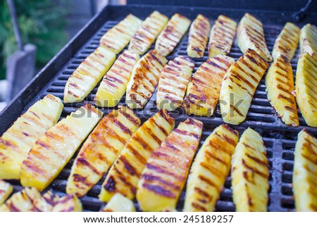 Fried pineapples on grill outdoor - stock photo