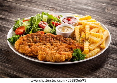 Fried pork chop, boiled potatoes and vegetable salad - stock photo