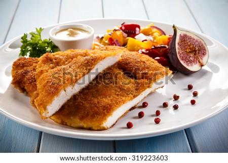 Fried pork chop coat in breadcrumbs and vegetable salad  - stock photo