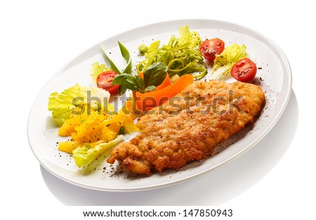 Fried pork chops, baked potatoes and vegetable salad - stock photo