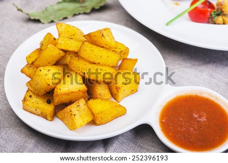Fried potato cubes  with sauce on a wooden table - stock photo